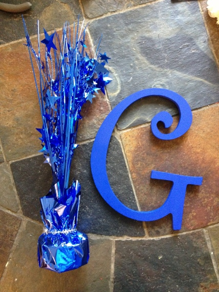 Blue flare and painted wooden letter G.
